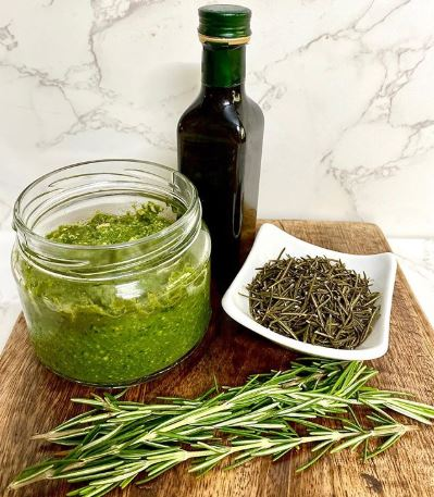 Clear glass jar of green pesto, fresh rosemary, dried rosemary and a bottle of olive oil on a wooden board