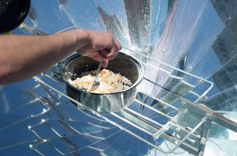 Free image from Canva of a pot cooking inside a reflective solar oven