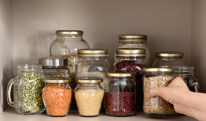 Free image from canva of glass jars with grains and pulses in them in an open cupboard