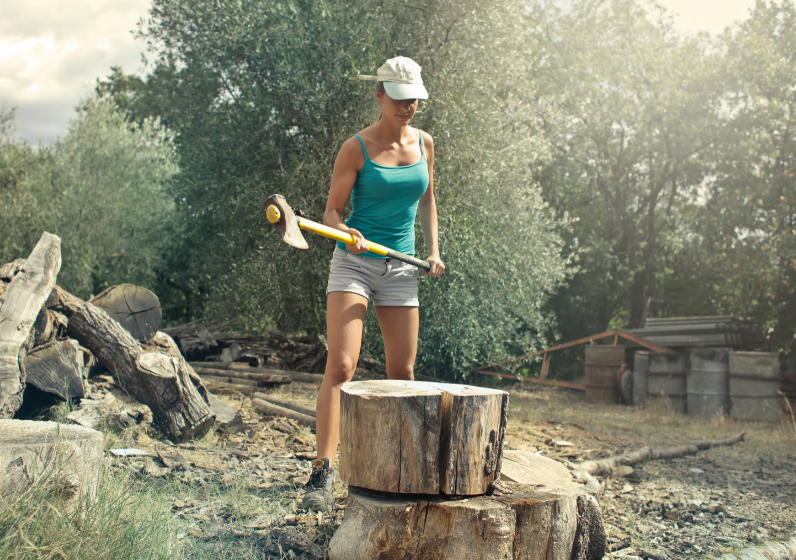 Living off the grid - free image from Canva of a young woman chopping wood with an axe
