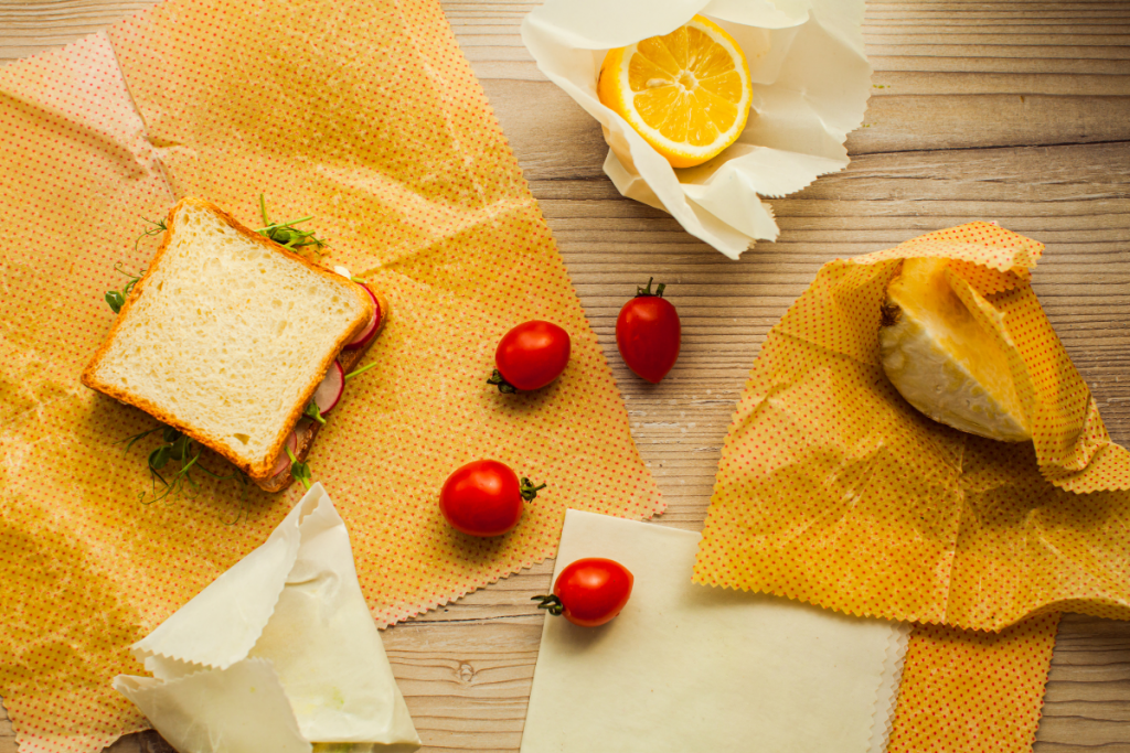 Eco Swaps - Free Canva Image of Yellow Beeswax Wraps with a sandwich, cherry tomatoes and a lemon on a wooden cutting board