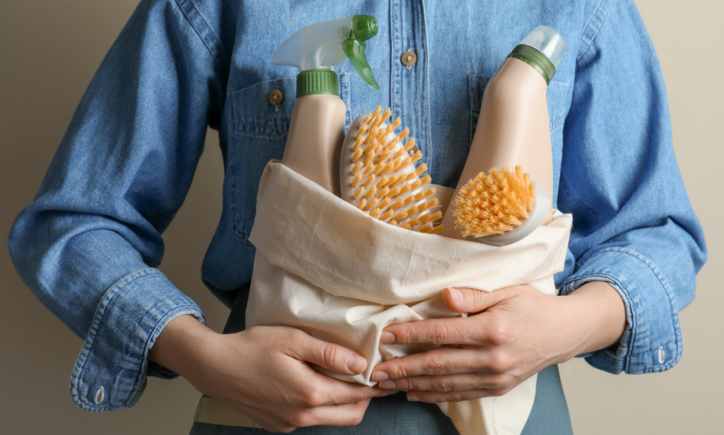 Eco Swaps - Image from Canva of a woman in a blue denim short holding some Eco Friendly Cleaning Products