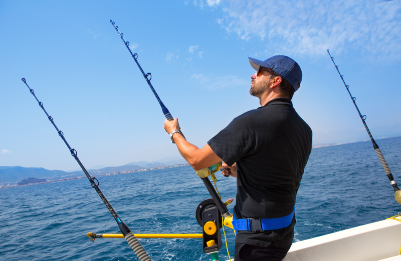Sustainable Fishing Methods - stock image of a man in a boat fishing with a rod