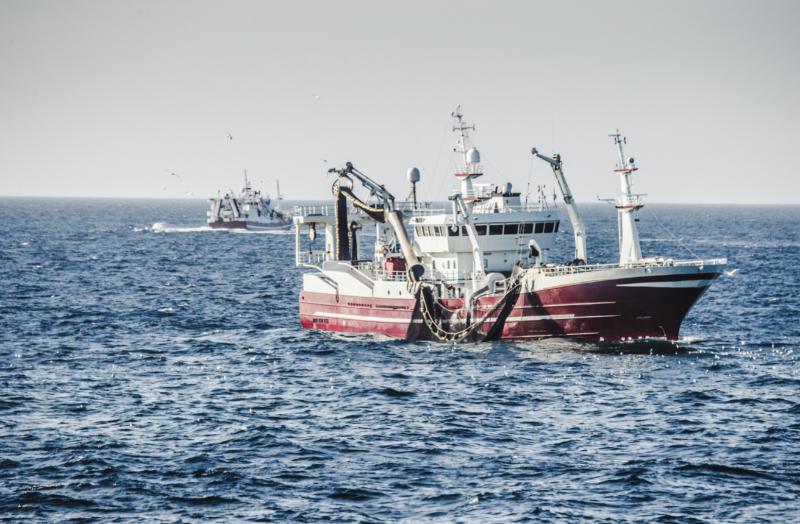 Sustainable Fishing Methods - stock image of a shipping vessel using a purse seine net