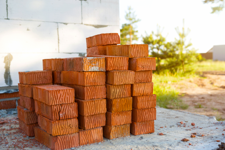 Storing Building Materials - Stock Image from Canva of a small stack of bricks outside a house