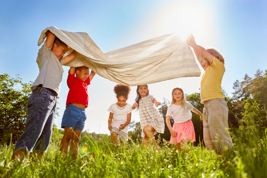 Teaching Kids About Sustainability - Group of happy kids playing in a field with a towel held up like a tent over them