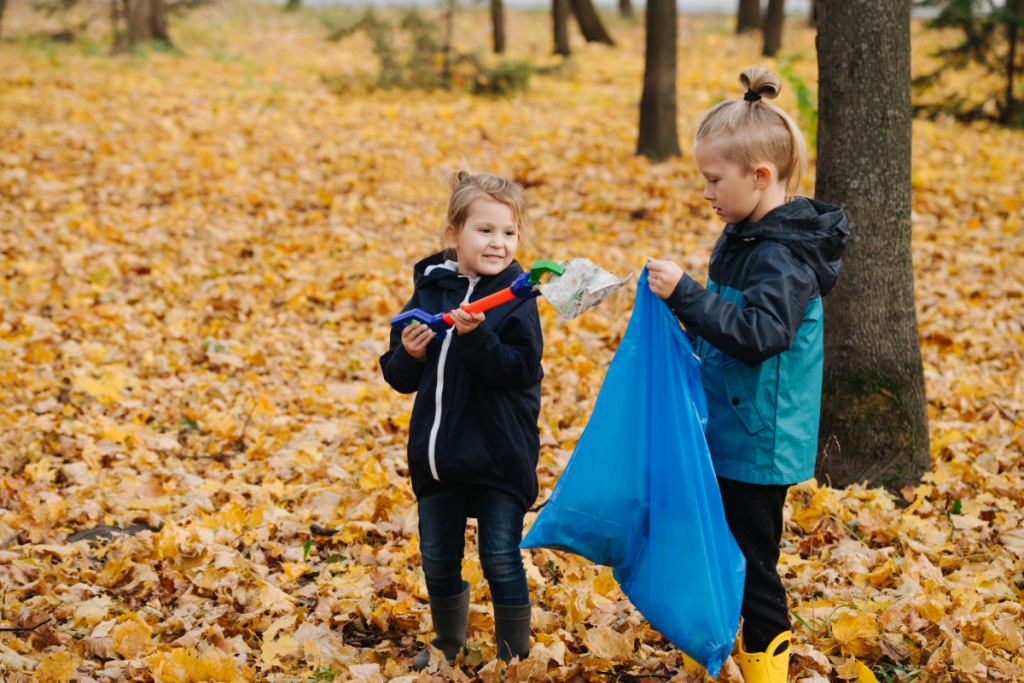 Teaching kids about sustainability - two kids in a park picking up litter with a grabby stick