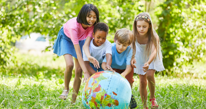 Teaching Kids About Sustainability - Group of kids playing with a ball that is a map of earth outdoors - Stock image from Canva